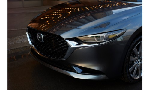2019 Mazda3 sedan exterior shot with gray metallic paint color closeup of front fascia, hood, headlights, and grille