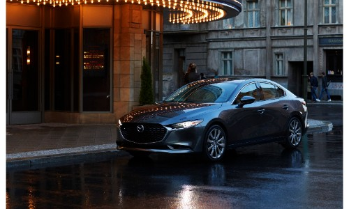2019 Mazda3 sedan exterior shot with gray metallic paint color parked on a rainy street underneath a lit up theater sign