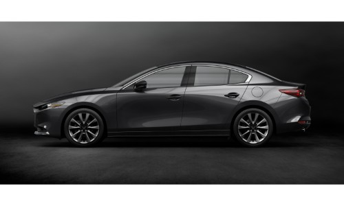 2019 Mazda3 sedan exterior side shot with black paint color parked in a blank black showroom