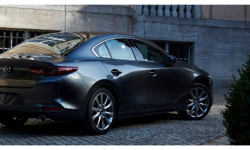 2019 Mazda3 sedan exterior side shot with gray metallic paint color parked on a tile road near bushes