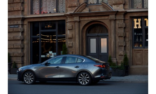 2019 Mazda3 sedan exterior side shot with gray metallic paint color parked outside an old stone building