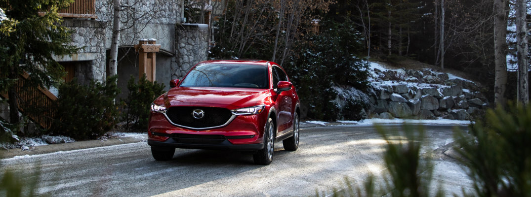 2019 Mazda CX-5 exterior front shot with soul red paint color parked outside a stone forest house