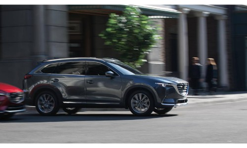 2019 Mazda CX-9 exterior side shot with gray paint color driving through a city intersection as the background blurs