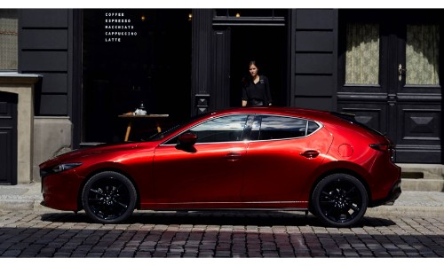 2019 Mazda3 Hatchback exterior side shot with red paint color parked on a tile street as its driver approaches