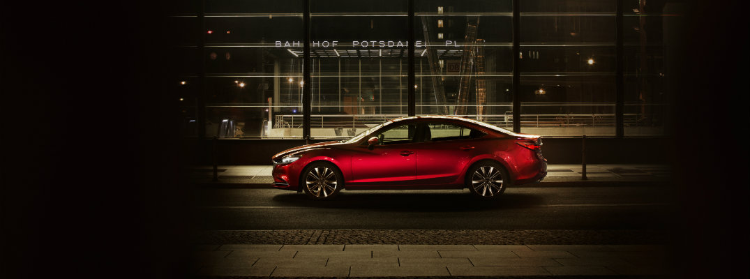 2018 and 2019 Mazda6 exterior side shot with red paint color parked outside an airport at night