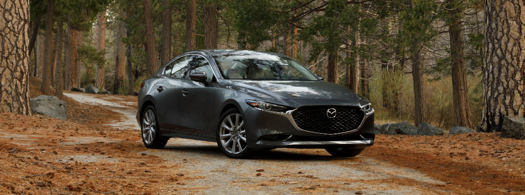 2019 Mazda3 sedan exterior shot with gray metallic paint color parked on a dirt path within an open forest