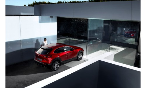 2020 Mazda CX-30 compact crossover SUV overhead rear shot with soul red crystal paint color parked in a fancy glass building as a women enters the driver's door small
