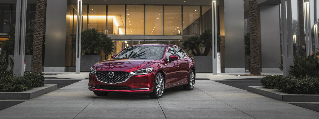 2019 Mazda6 exterior shot with soul red crystal paint color parked outside the plaza of a fancy hotel with palm trees