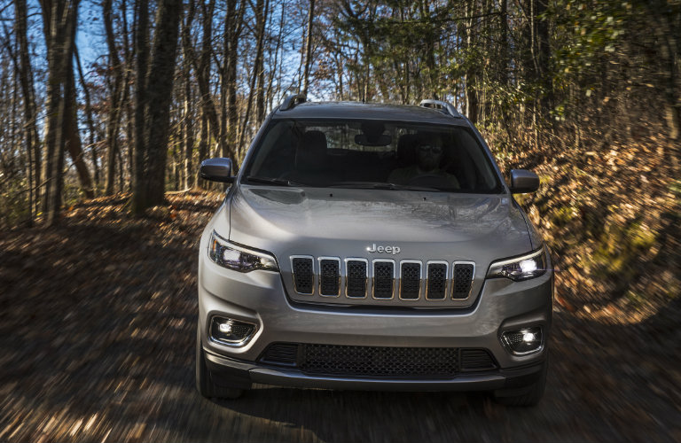 front view of the 2019 Jeep Cherokee driving down a forest path in the fall