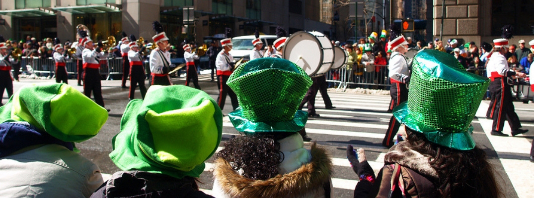 Group of spectators in green top hats watching marching band in parade