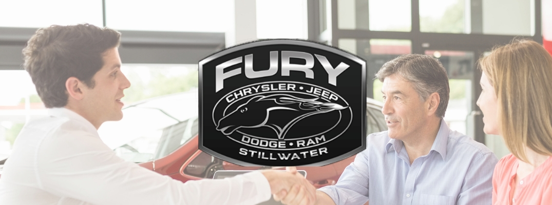 Salesman shaking customers hand with Fury Motors Stillwater logo over the photo