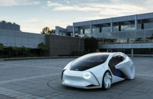 Toyota Concept-i vehicle parked in front of a modern concrete building with a lot of windows
