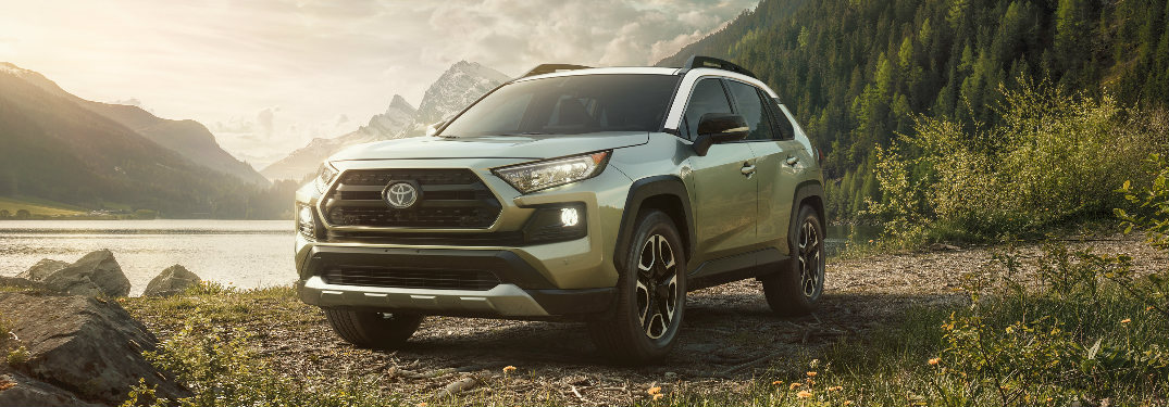 2019 Toyota RAV4 parked on a gravel lot in front of a lake that is surrounded by mountains