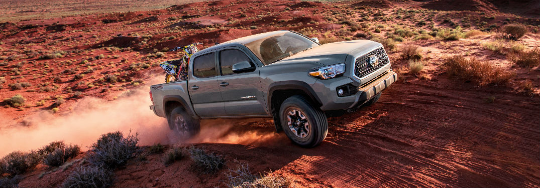 2018 Toyota Tacoma climbing a hill and kicking up red dust in the desert
