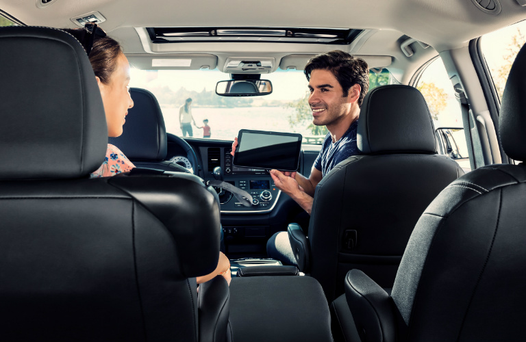 Man holding tablet in the front seat of the 2019 Toyota Sienna