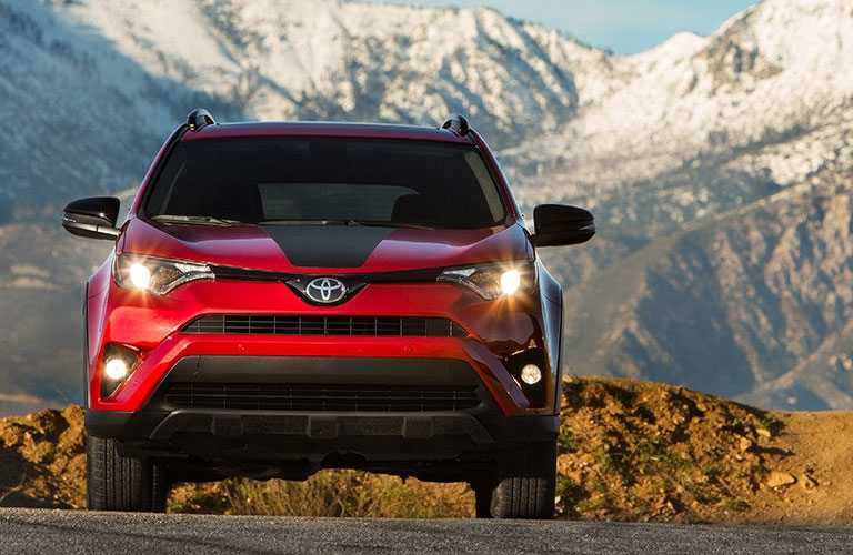 2018 Toyota RAV4 in red parked at the base of snowy mountains