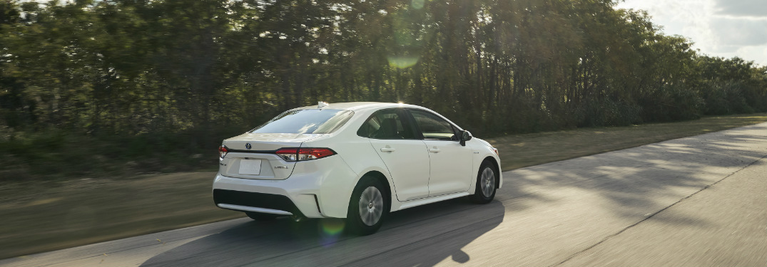 2020 Toyota Corolla Hybrid in white driving down an empty road