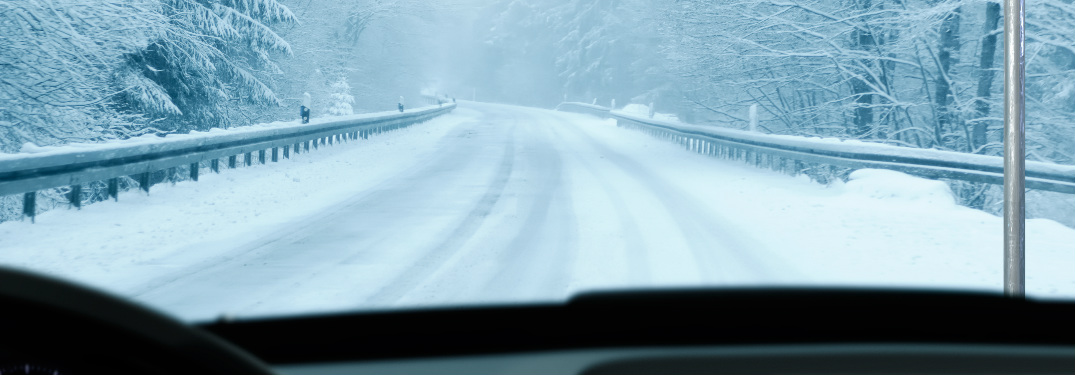 View out the windshield of an empty snowy road