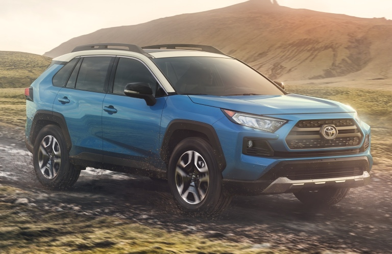 2019 Blue Rav4 Hybrid with hill in background