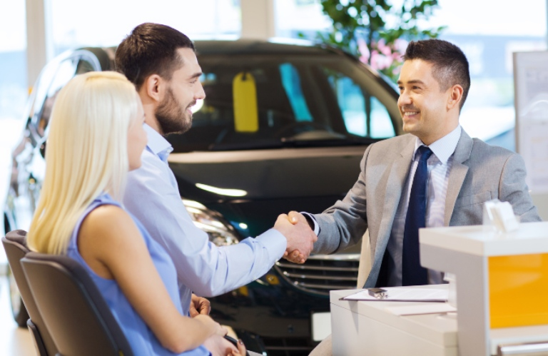 Two people buying a vehicle and two men shaking hands