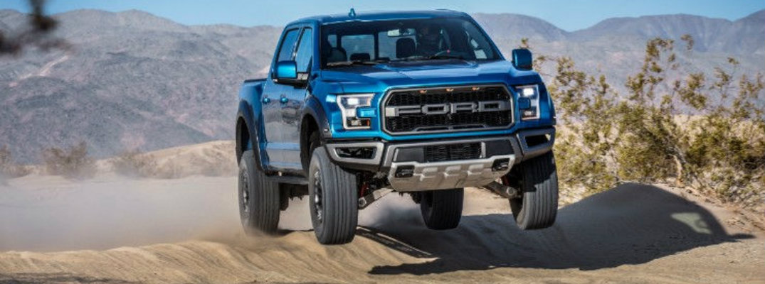 2019 Ford F-150 Raptor driving over hill in daytime