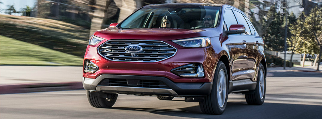 Red 2019 Ford Edge driving on busy city street