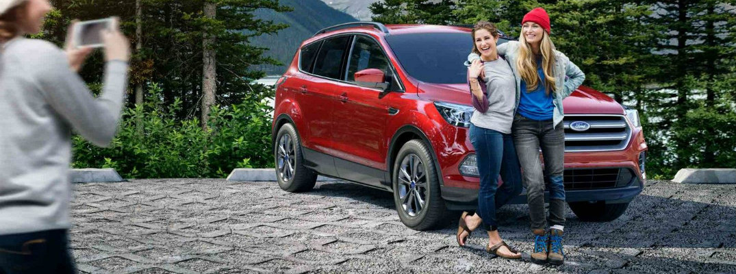 Two girls taking picture in front of red 2018 Ford Escape