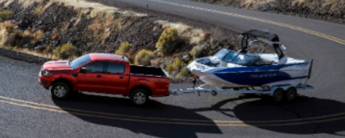 Red 2019 Ford Ranger towing trailer around hairpin turn on highway