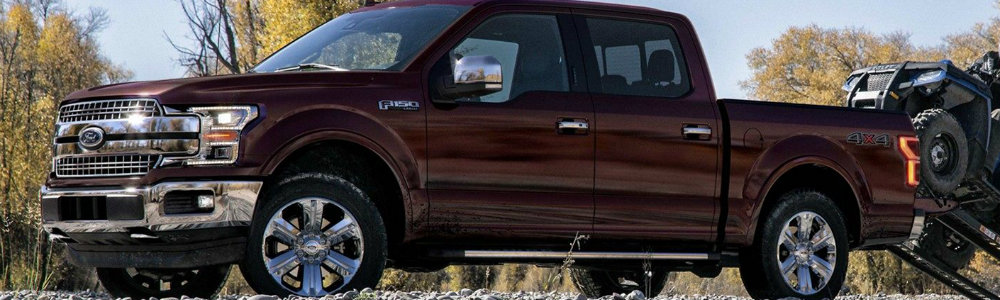 Profile view of burgundy 2019 Ford F-150 parked on gravel