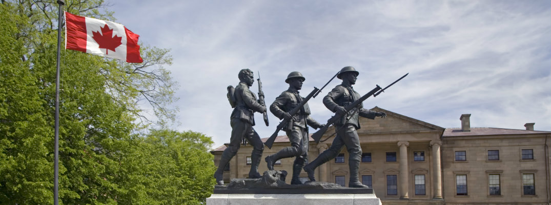 Statue with three soldiers positioned next to Canadian flag