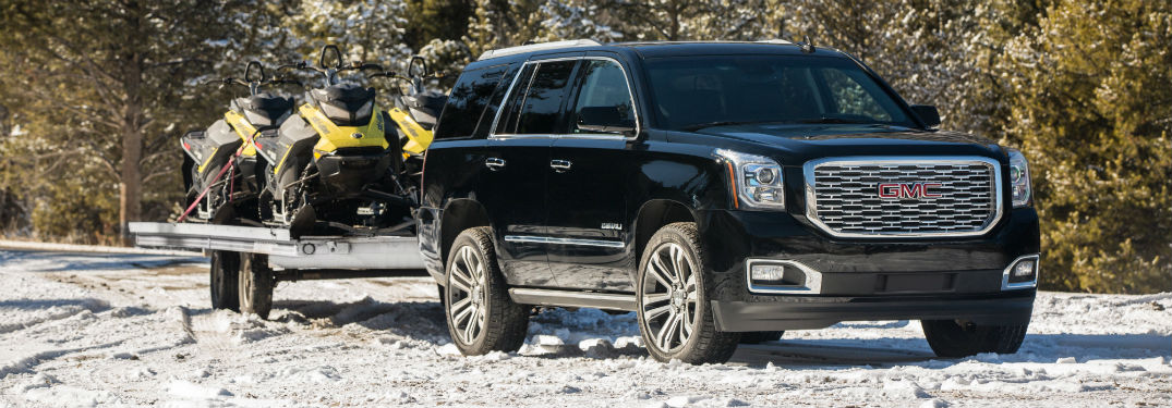 Passenger side view of a black 2018 GMC Yukon hauling snowmobiles