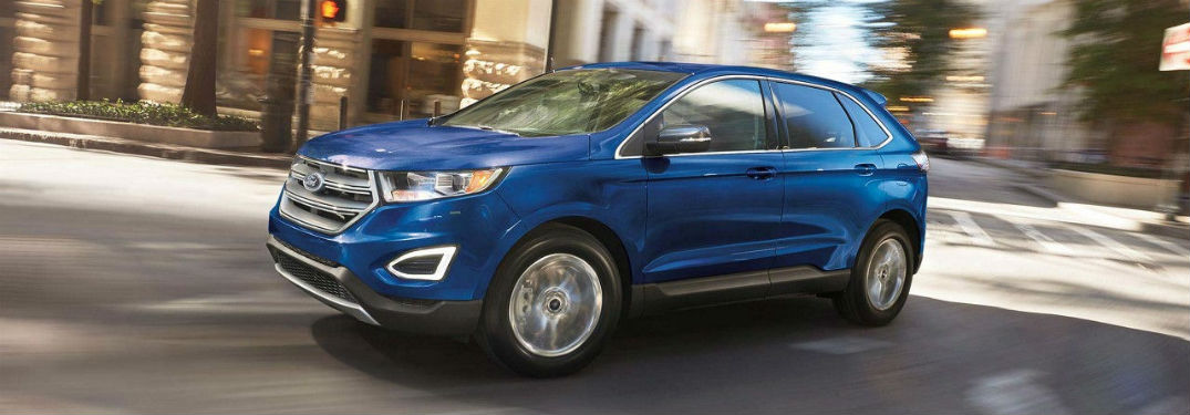 Driver side exterior view of a blue 2018 Ford Edge