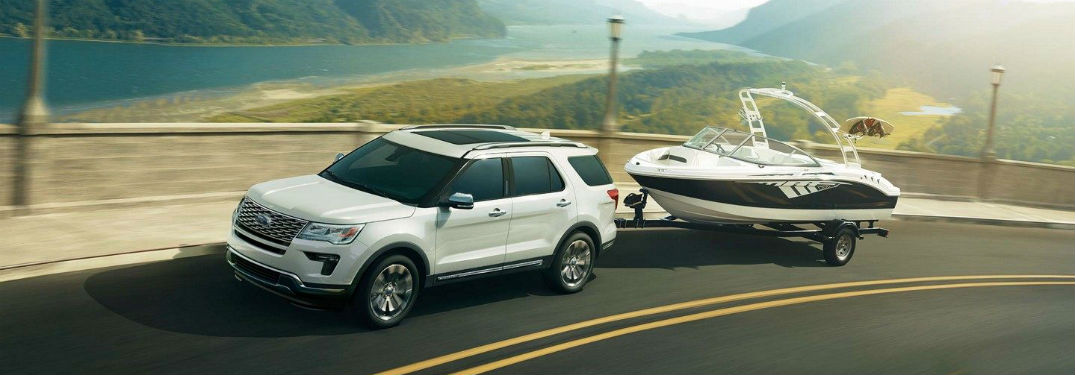 Driver side exterior view of a white 2018 Ford Explorer towing a boat