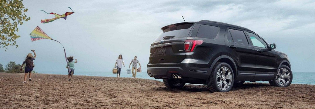Passenger side exterior view of a black 2019 Ford Explorer parked on a beach