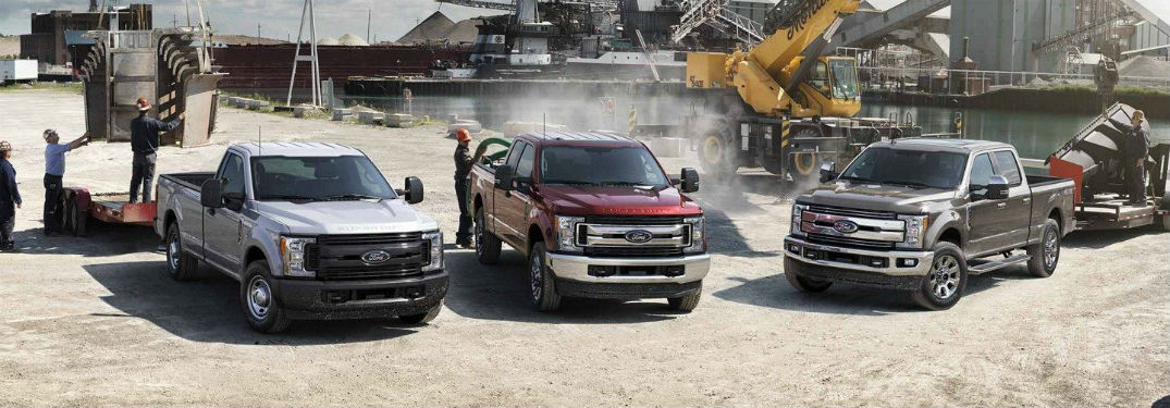 Front exterior view of three 2019 Ford F-250 pickup trucks at a work site