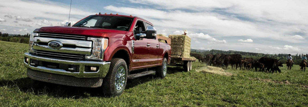 Front exterior view of a red 2019 Ford F-350 hauling a trailer of hay bails