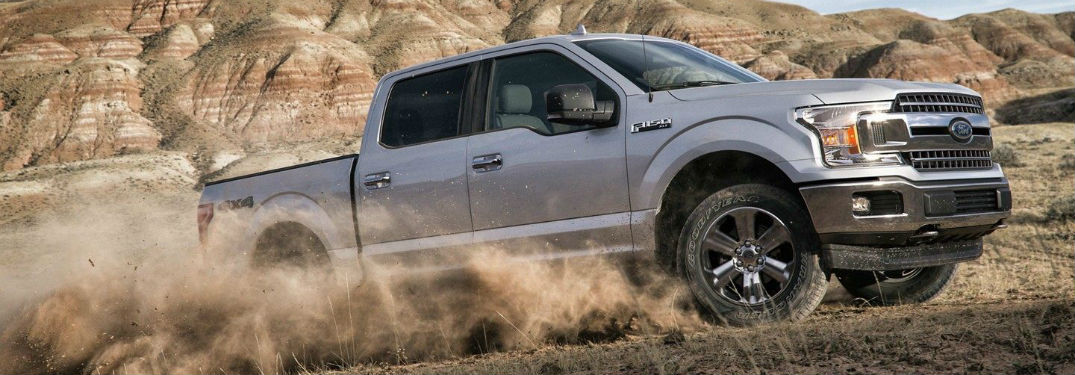Passenger side exterior view of a gray 2019 Ford F-150 kicking up dirt as it drives through the desert