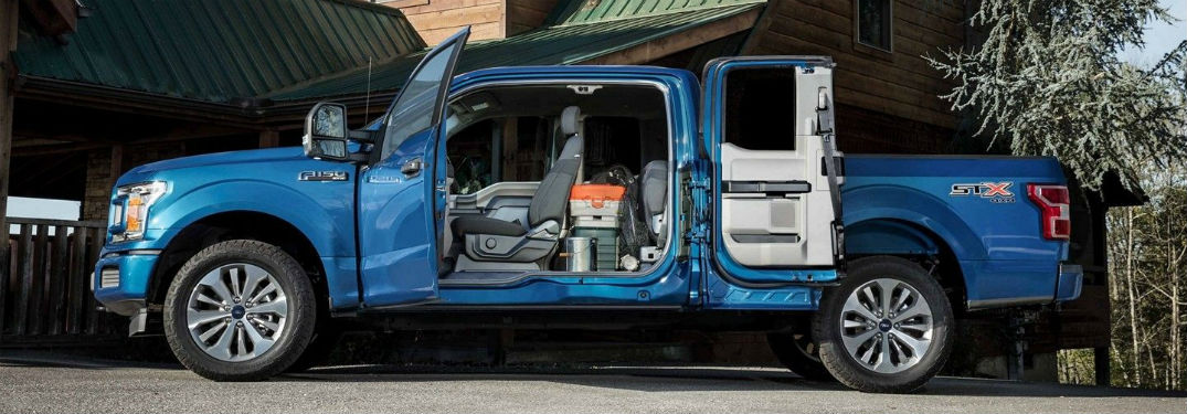 Driver side exterior view of a blue 2019 Ford F-150 with its door wide open showing its seating space and cargo versatility