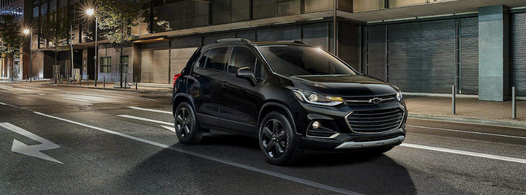 2019 Chevrolet Trax exterior shot with black paint color parked on a city street at night under street lights