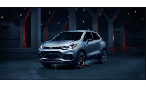 2019 Chevy Trax exterior shot with gray silver paint color parked inside a dark warehouse with red lighting in the background
