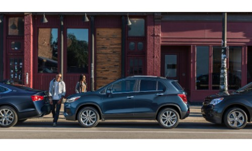 2019 Chevy Trax exterior side shot with dark blue metallic paint color parked between other cars as a couple approaches