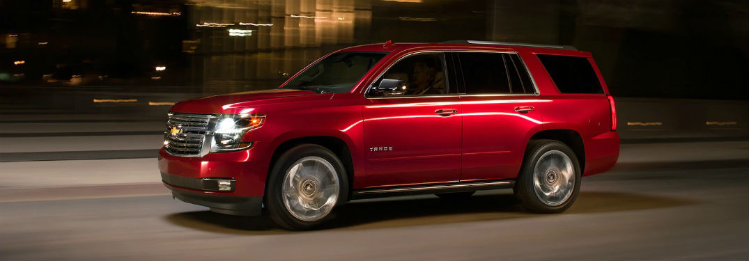 Driver side exterior view of a red 2019 Chevy Tahoe