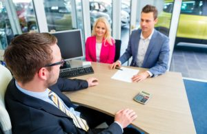 man and woman at car salesman's desk