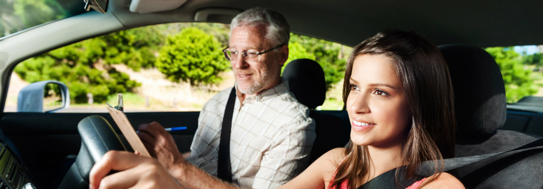girl driver and driving instructor in front seats of a car