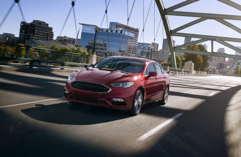 front view of red ford fusion driving on bridge