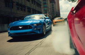front view of blue ford mustang driving on city road