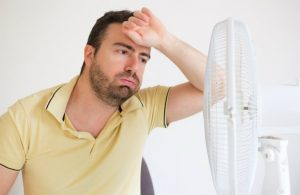 man hot and wiping forehead in front of fan