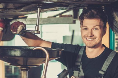 A smiling man opens up a valve underneath a vehicle as he performs maintenance.