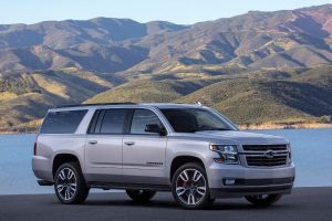 2020 Chevy Suburban parked in front of a lake with hills in background from exterior front passenger angle_o