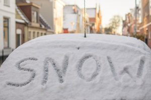 Image of a car covered in snow with SNOW written on back windshield_c